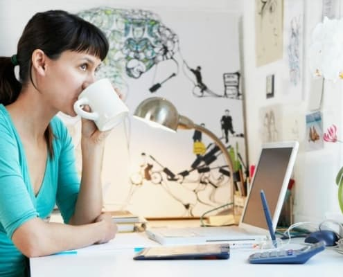 young woman drinking coffee at desk, looking out window thinking about best financial decisions