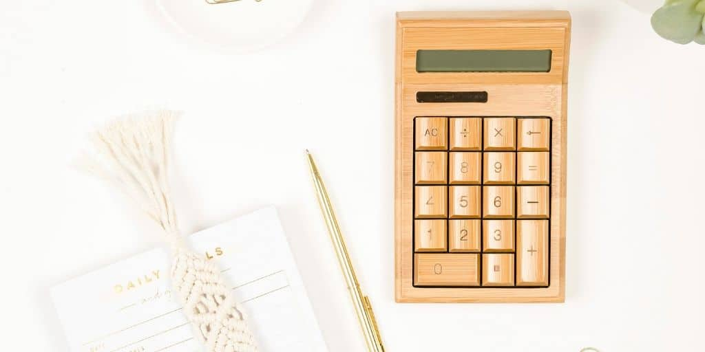wooden calculator on white desk, flatlay