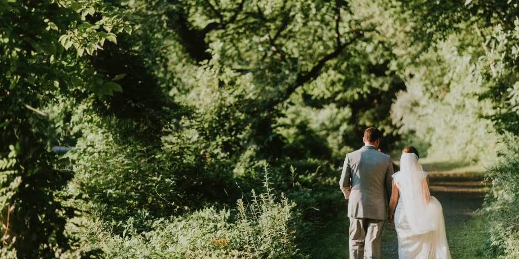 a bride and groom walking in forest, hoping to avoid financial marriage problems