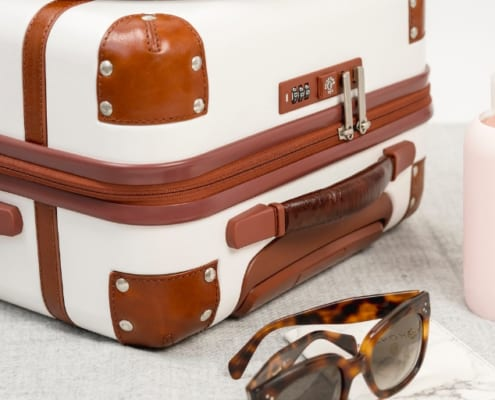 white luggage with leather accessories, sunglasses, bottle of water, to be used with free airline tickets