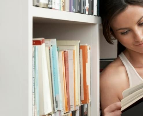 young woman reading used book, leaning on book shelf