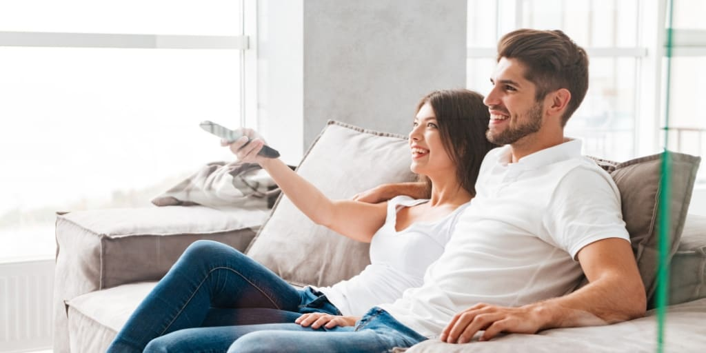 couple sitting on couch with tv remote