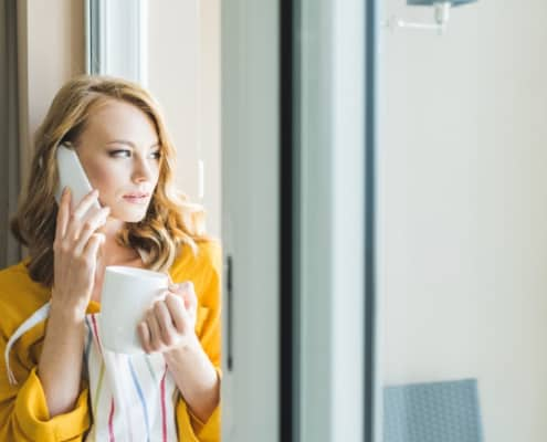 woman with yellow sweater on phone, looking anxiously out window, deal with debt collectors