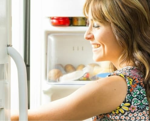 mother opening up freezer to pick healthy freezer meal