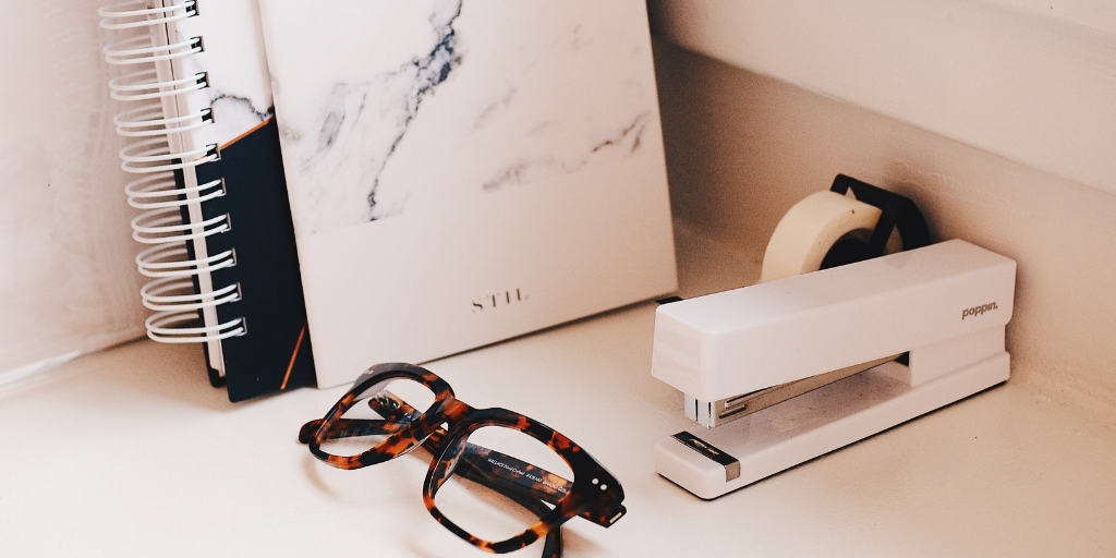 pink marble desktop with glasses, books, and stapler
