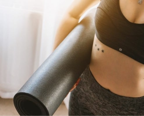 young woman in gym outfit, holding yoga mat, at gym