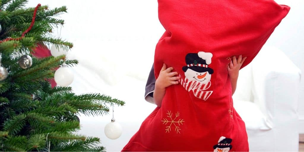 person with big Santa bag full of gifts they can't carry