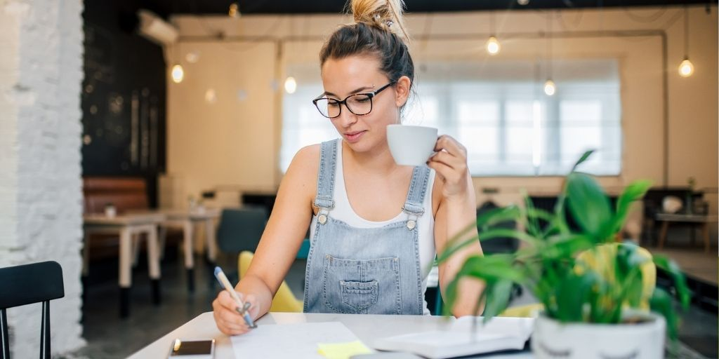 woman in her thirties at desk with coffee smiling while working on how to save money on health insurance premiums