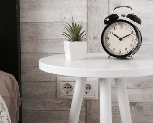 white bedside table with old fashioned clock and succulent plant