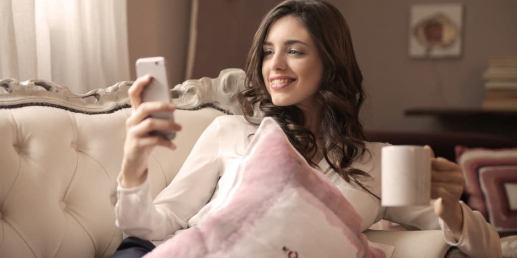 woman on pink chaise looking at opportunities on phone