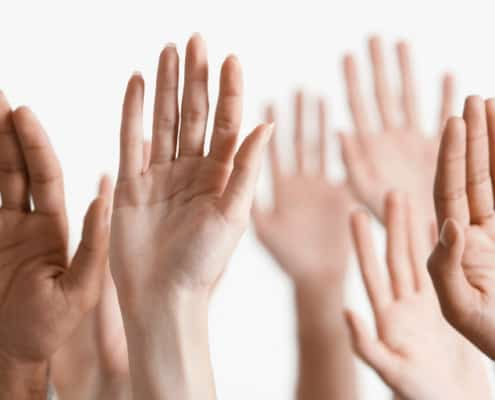 group of hands of all nationalities raised to volunteer, on white background