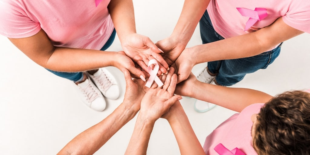 a group of females wearing pink shirts holding a pink cancer ribbon together