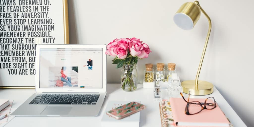 white desk with laptop, gold lamp, pink flowers