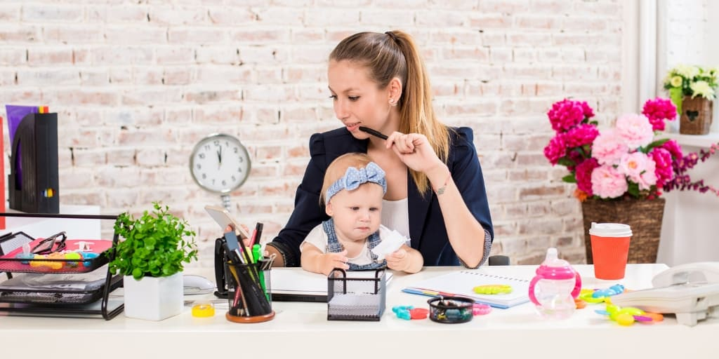 young woman with baby in lap working from home at desk