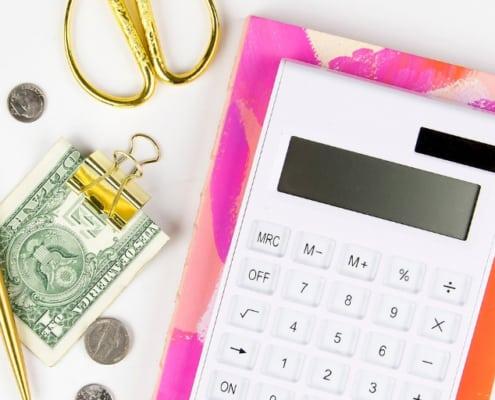white desktop with calculator, money in clip, gold scissors