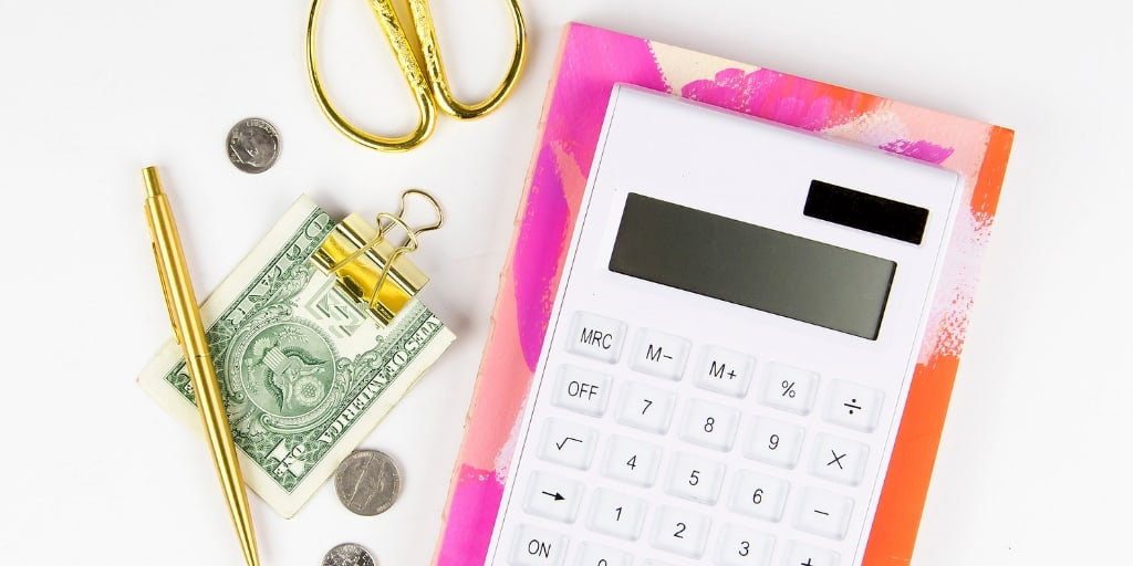 white desktop with calculator, money in clip, gold scissors