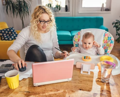 woman with glasses working on laptop at kitchen table with baby