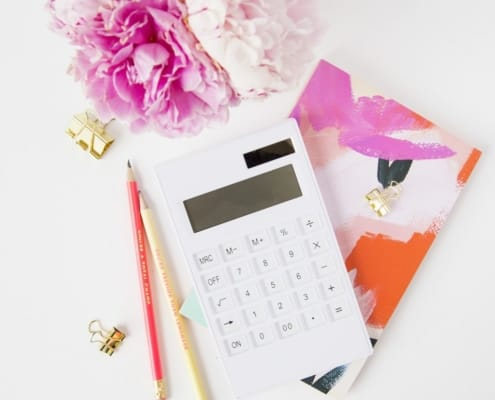 white desktop with peonies, and a calculator to help dispute a medical bill