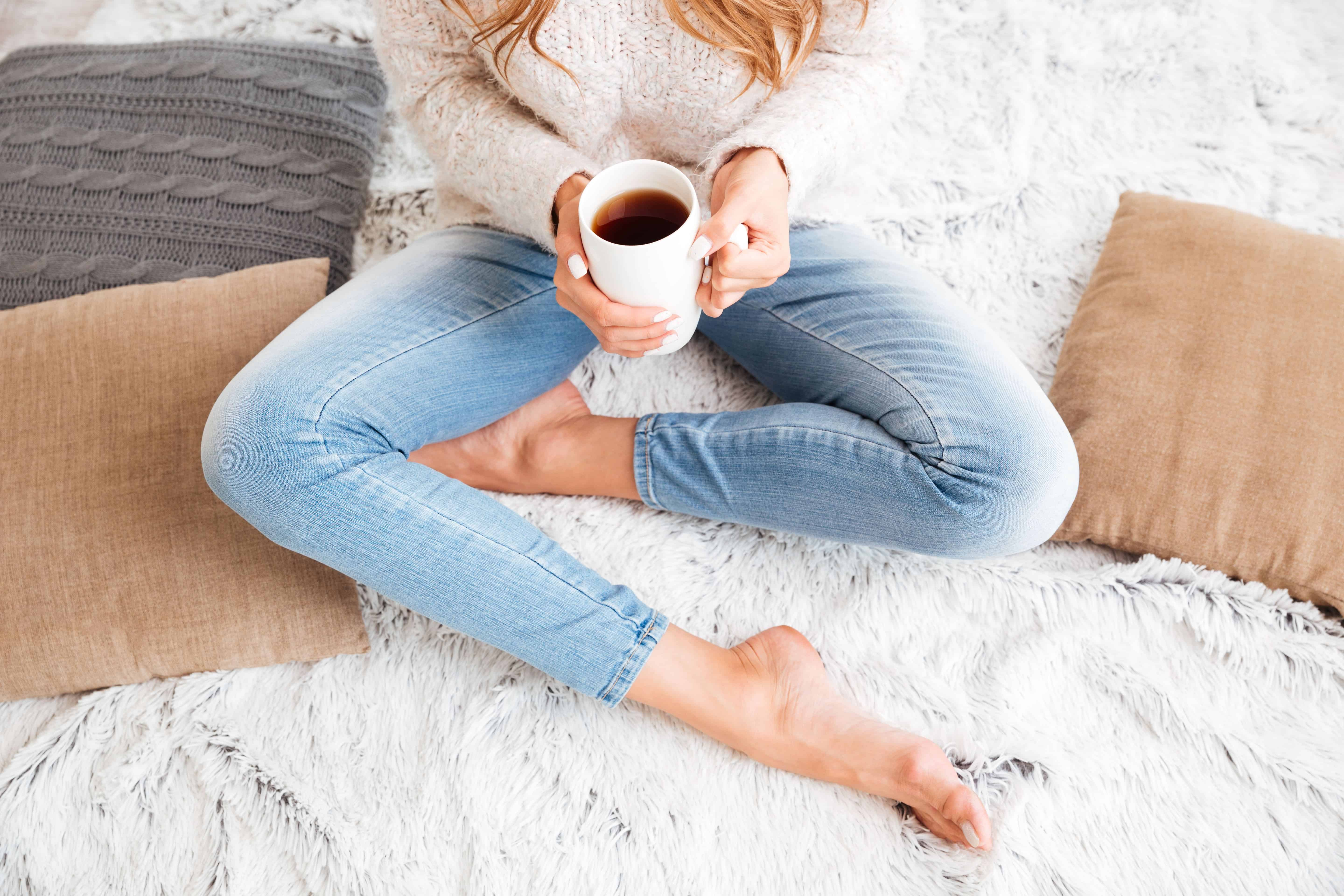 woman in sweater and jeans holding hot tea sitting
