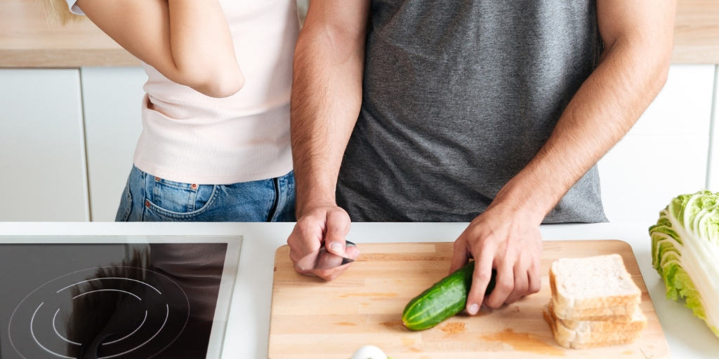 a couple in the kitchen, flirting and cooking