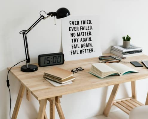 wooden desktop with lamp and motivational poster