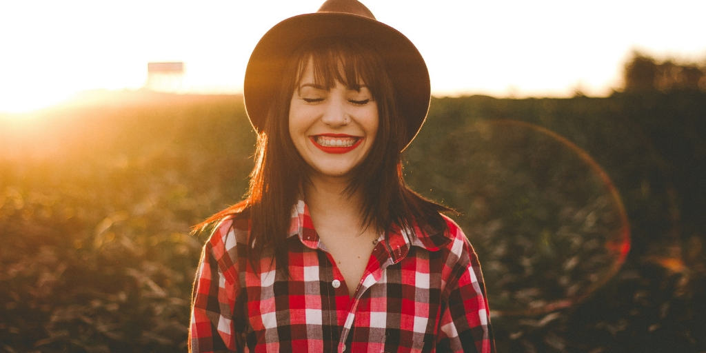 woman in field with sun going down, hat on, smiling