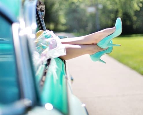 woman's legs with high heels dangling out of car window