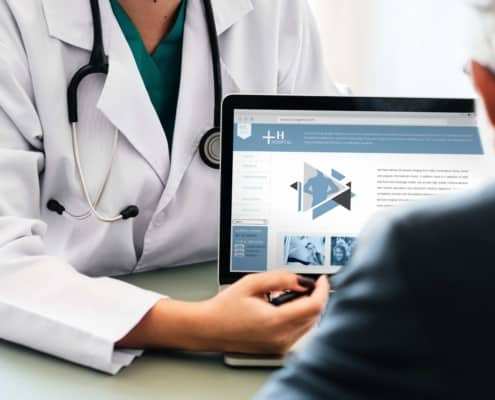 doctor with laptop going over a medical bill in collection with patient