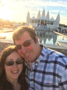 picture of author and husband smiling together in front of Indian temple