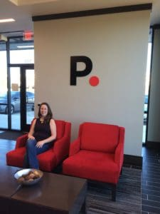 author sitting in red chair in PurePoint bank lobby