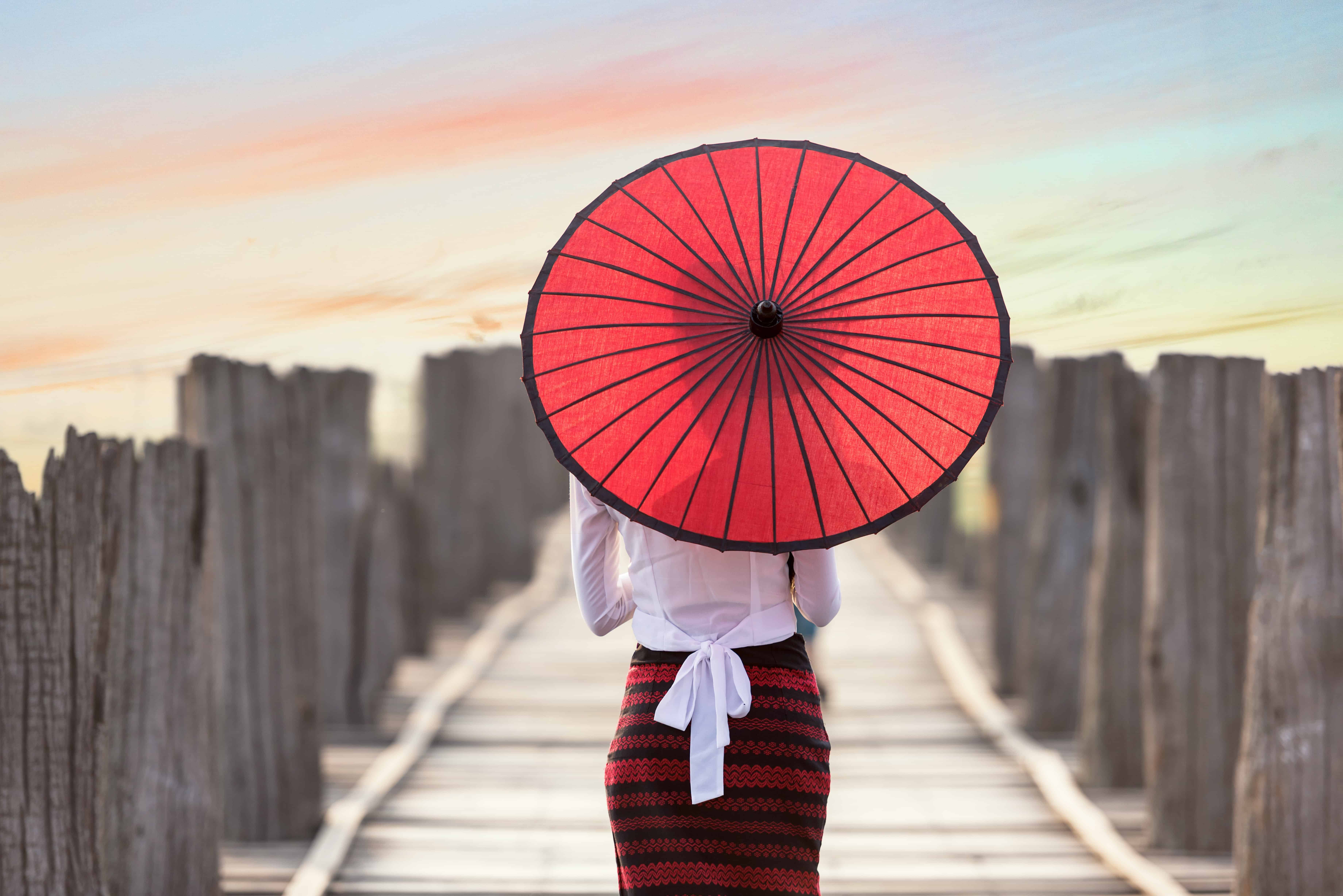 woman with pencil skirt and red Asian umbrella walking down dock