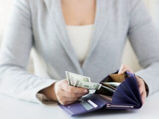 woman in light blue blazer, pulling cash out of navy blue wallet to avoid common budget pitfalls