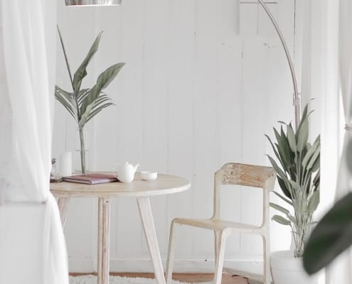 sitting area in a white room, with a lamp, plant, and table with chair