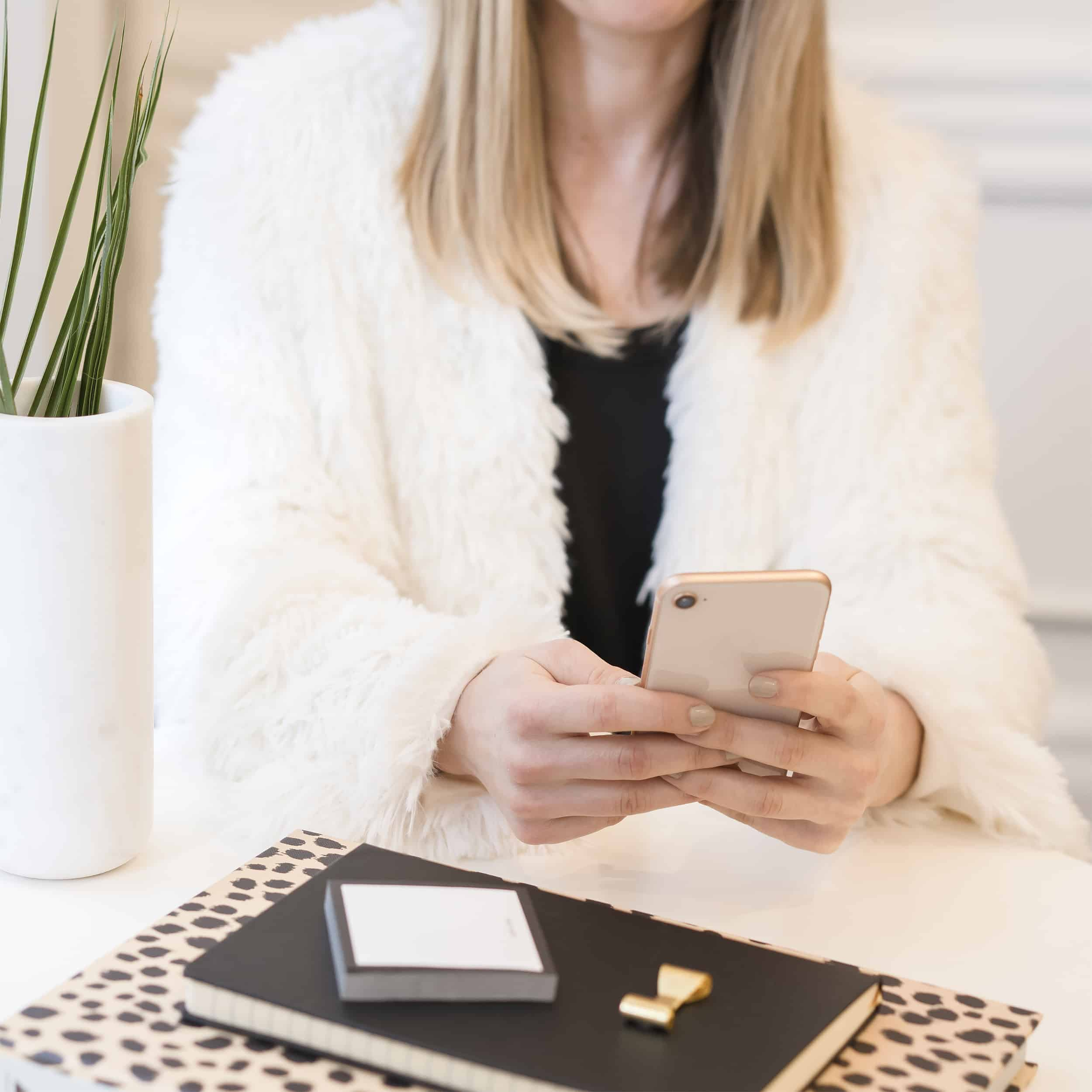 woman on her phone, sitting at desk, with leopard notepad