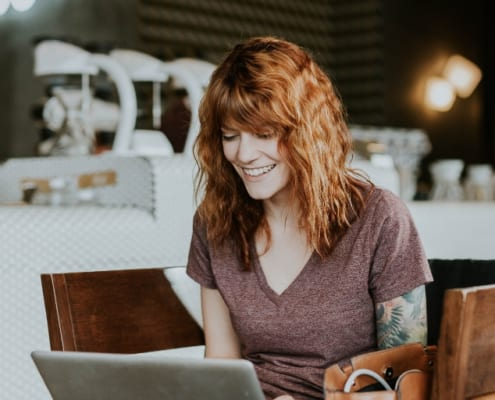 woman happily working on laptop at a coffee shop towards financial independence