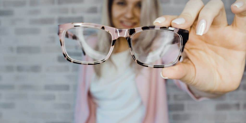 woman on brick background, holding pink and black reading glasses to camera