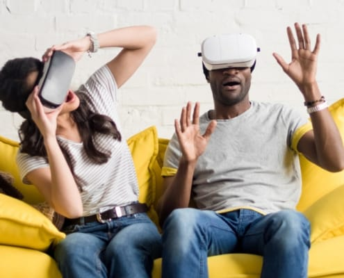 couple sitting on yellow sofa, with virtual gear over their eyes