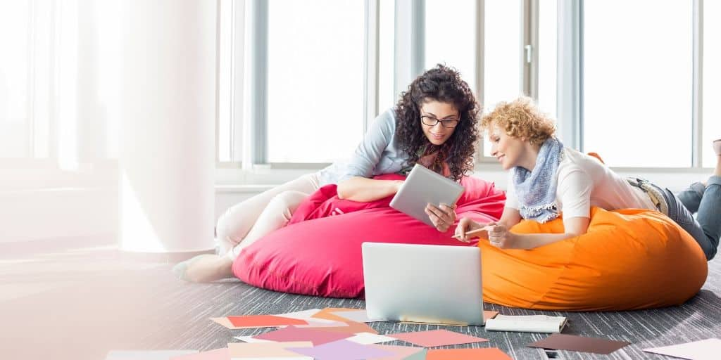 two women sitting on pink bean bag chair, looking at ipad screen together