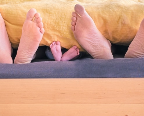 bed with three family member's feet hanging out