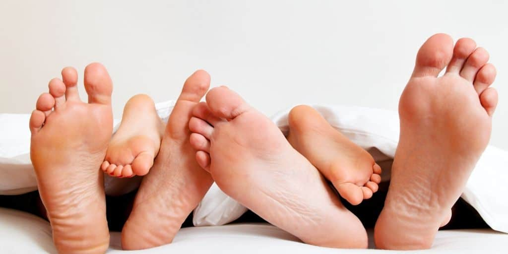 image of family feet, dad, mom, and toddler, on bed