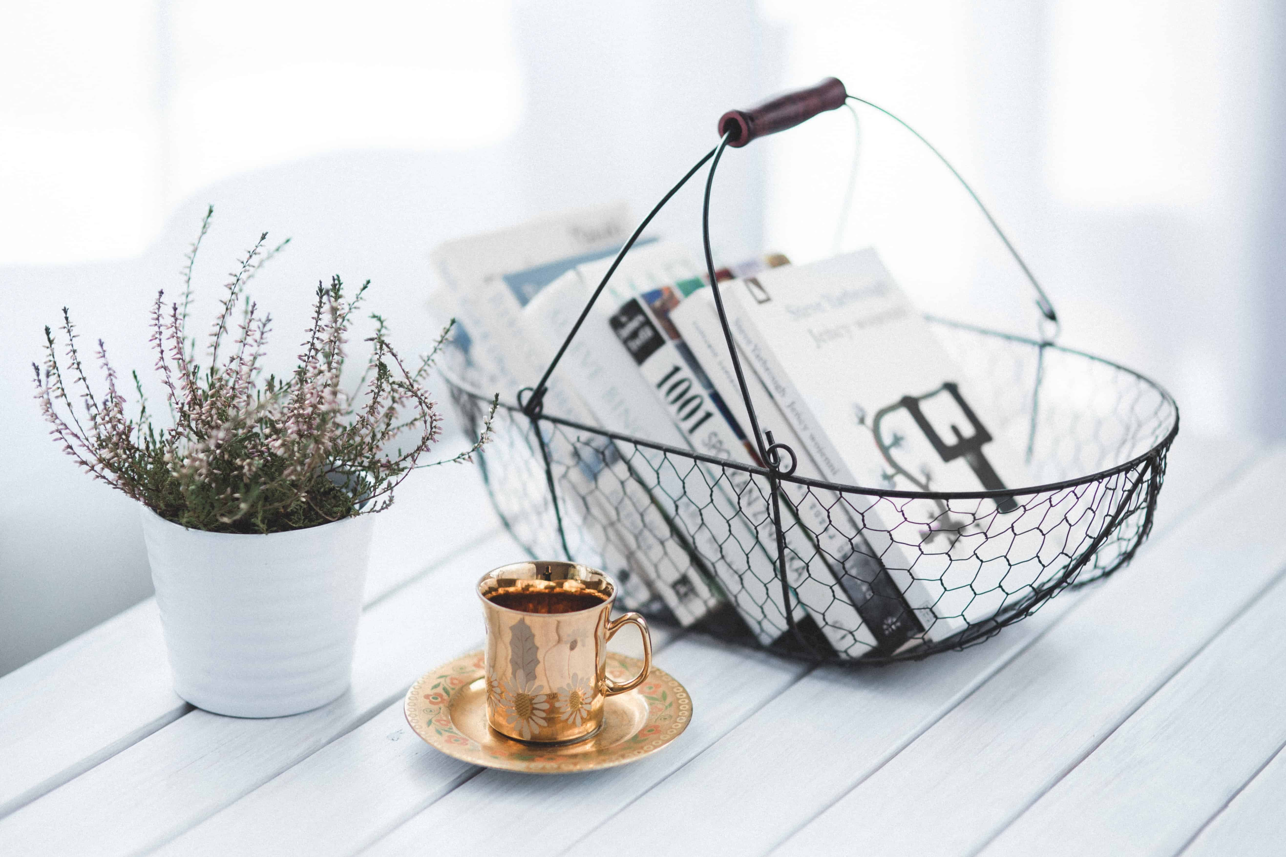 a basket with books, a copper coffee mug and plant on white table