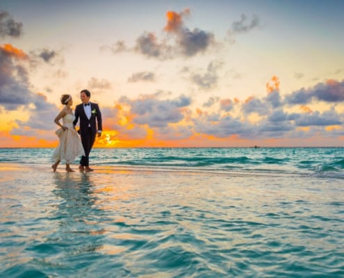 A bride and groom, walking along the beach and talking about marriage and finances