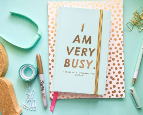 """pale blue desktop with pen and notepad that says """"I am very busy"""""""
