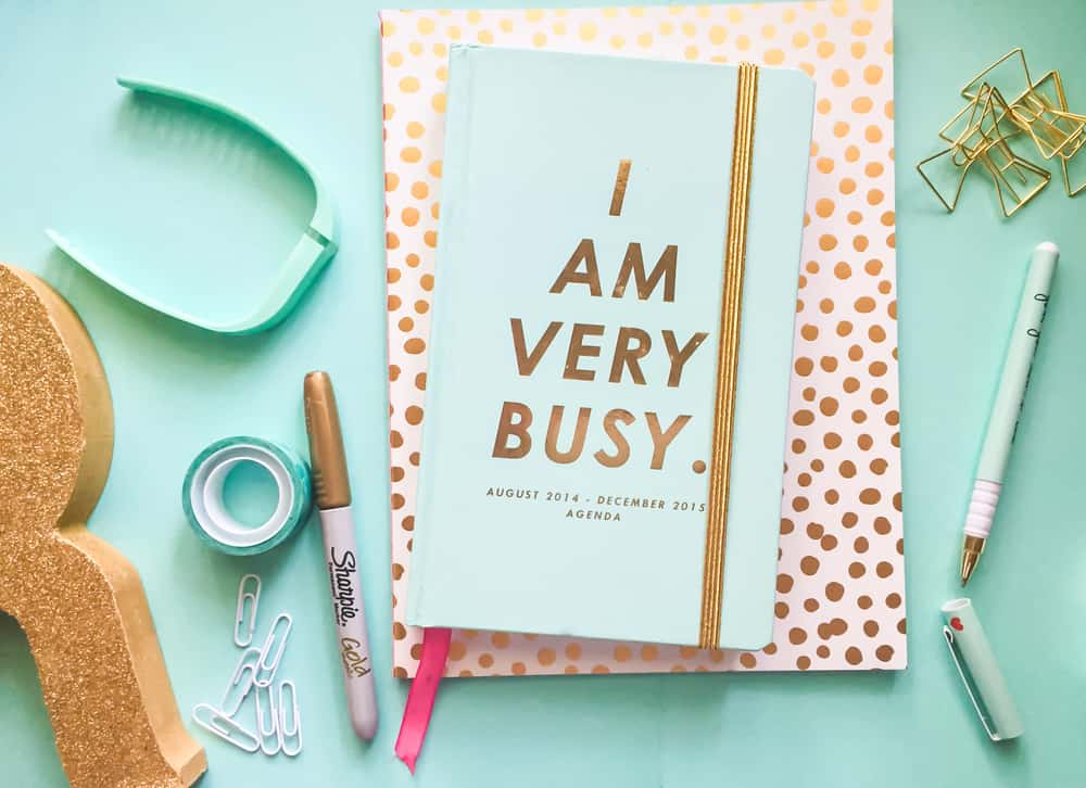 "pale blue desktop with pen and notepad that says ""I am very busy"""