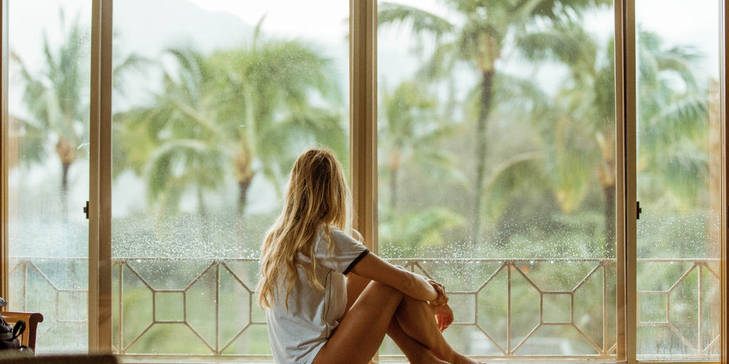 woman in tropical location, sitting on windowsill and staring outside