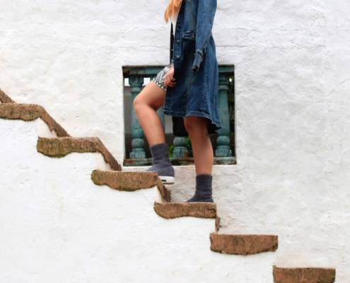 woman in boots and trench coat climbing stone stairs
