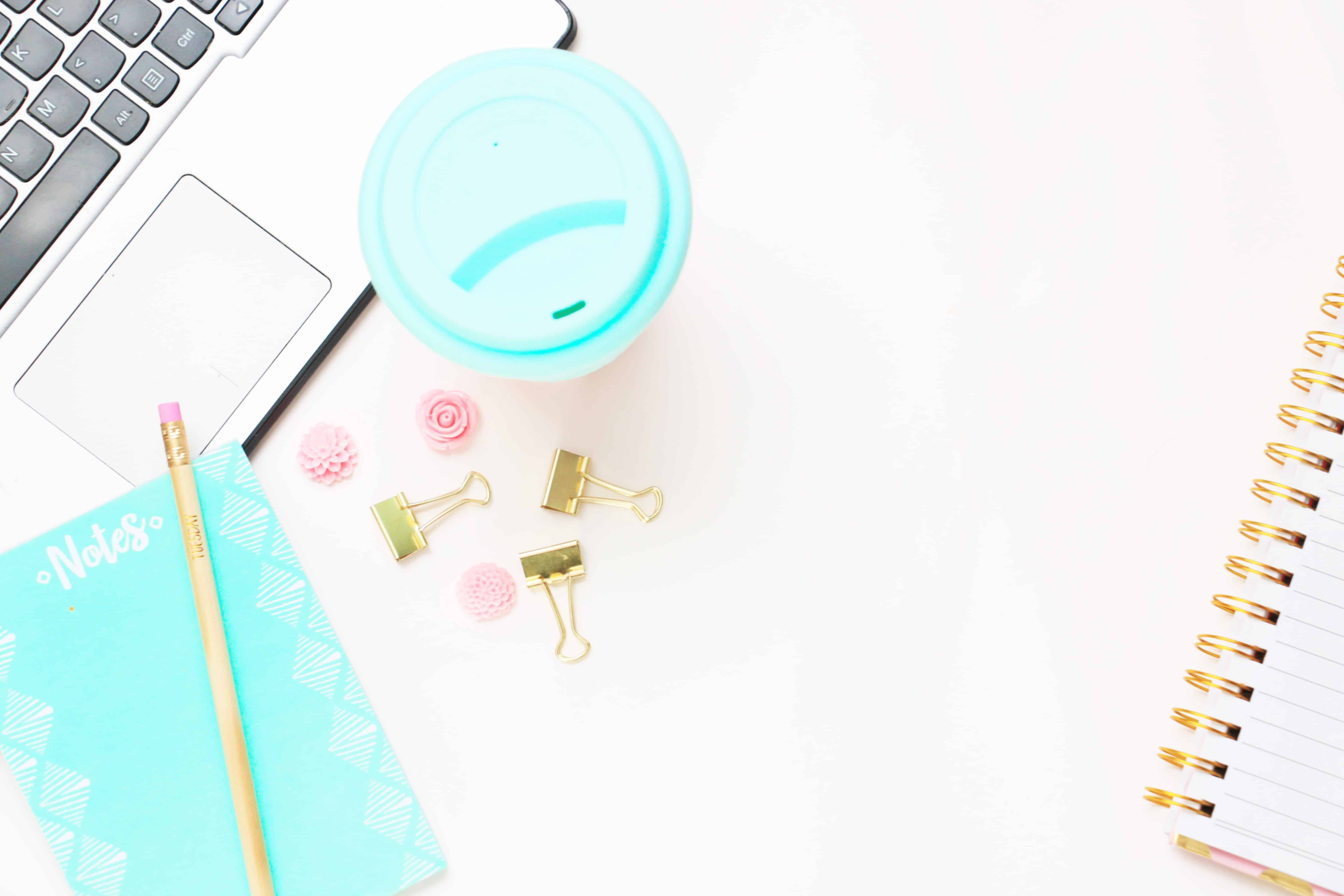 coffee with a light blue lid on a desk, with a laptop, and binder clips