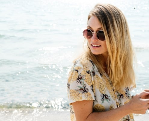 blonde woman looking over her shoulder at beach with iPhone