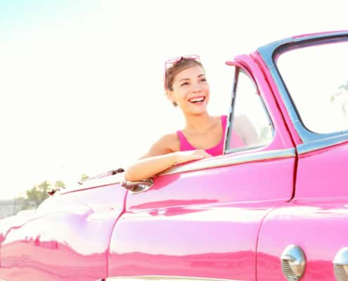 woman smiling driving a vintage pink cabriolet car