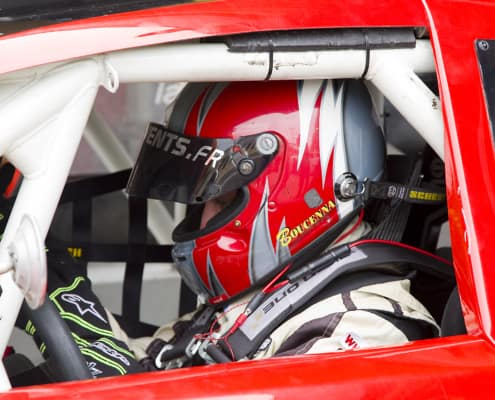 man in helmet driving a red race car